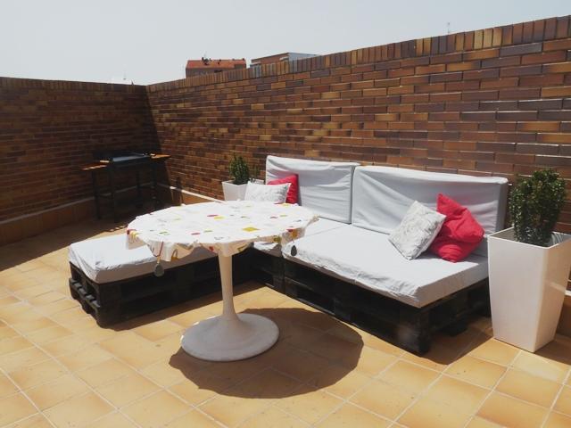 Una terraza con palets y cajas de frutas for Muebles terraza palets