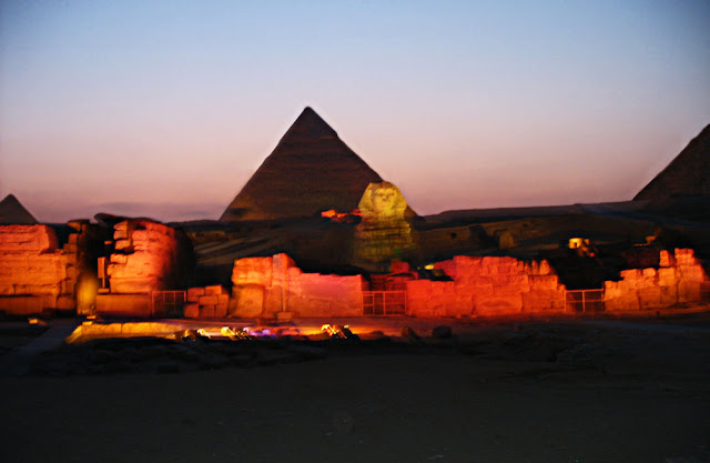 a glowing sphinx and the pyramid at night
