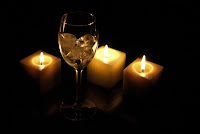 Wine glass with three candles standing behind it