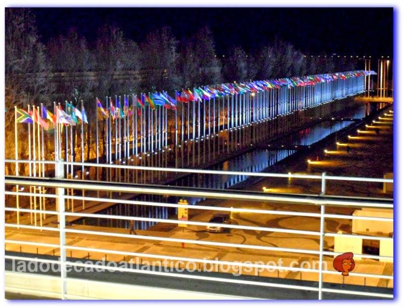 """Imagem da fileira de bandeiras de todas as nações em frente ao espelho d'água do passeio com o calçamento """"Mar Largo"""" de Fernando Conduto, Lisboa, Portugal"""