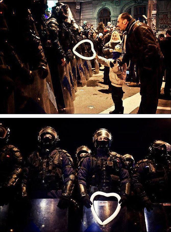 Мальчик предлагает шарик в форме сердца полицейскому во время протестов в Бухаресте, Румыния, 2012 год.
