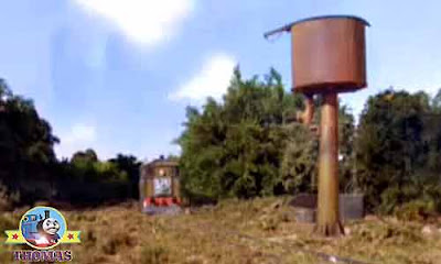 Tired Thomas and friends Toby the train engine stopped for a rest alongside a rusty old water tower