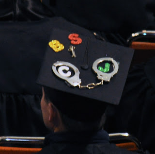 Graduation cap with CJ and cuffs written on it.