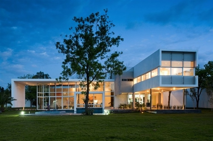 Beautiful white house by 7xa Taller de Arquitectura at night from backyard