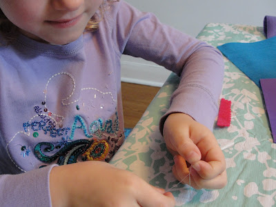 child threading a needle