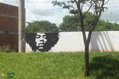 Jimi Hendrix painting on a wall, where the wall ends at top a tree continues his afro