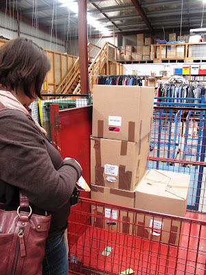 Woman looking at a trolley containing a stack of labelled cardboard cartons.