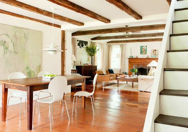 Dining room in a farmhouse with wood floor, reclaimed wood table, modern white seats, exposed beam ceiling and white pendant light