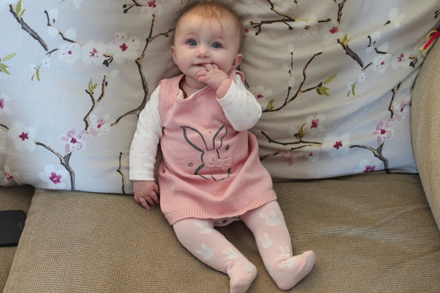 baby girl sat on sofa with fingers in mouth wearing pale pink tights with white bunnies on them, a long sleeved white vest with pale pink flower pattern and a knitted sleeveless pink dress with a bunny wearing  a bow