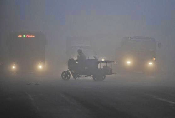 A tricycle travels past a crossroad on a hazy day in Hefei, Anhui province March 30, 2014. (Credit: Reuters/Stringer) Click to enlarge.