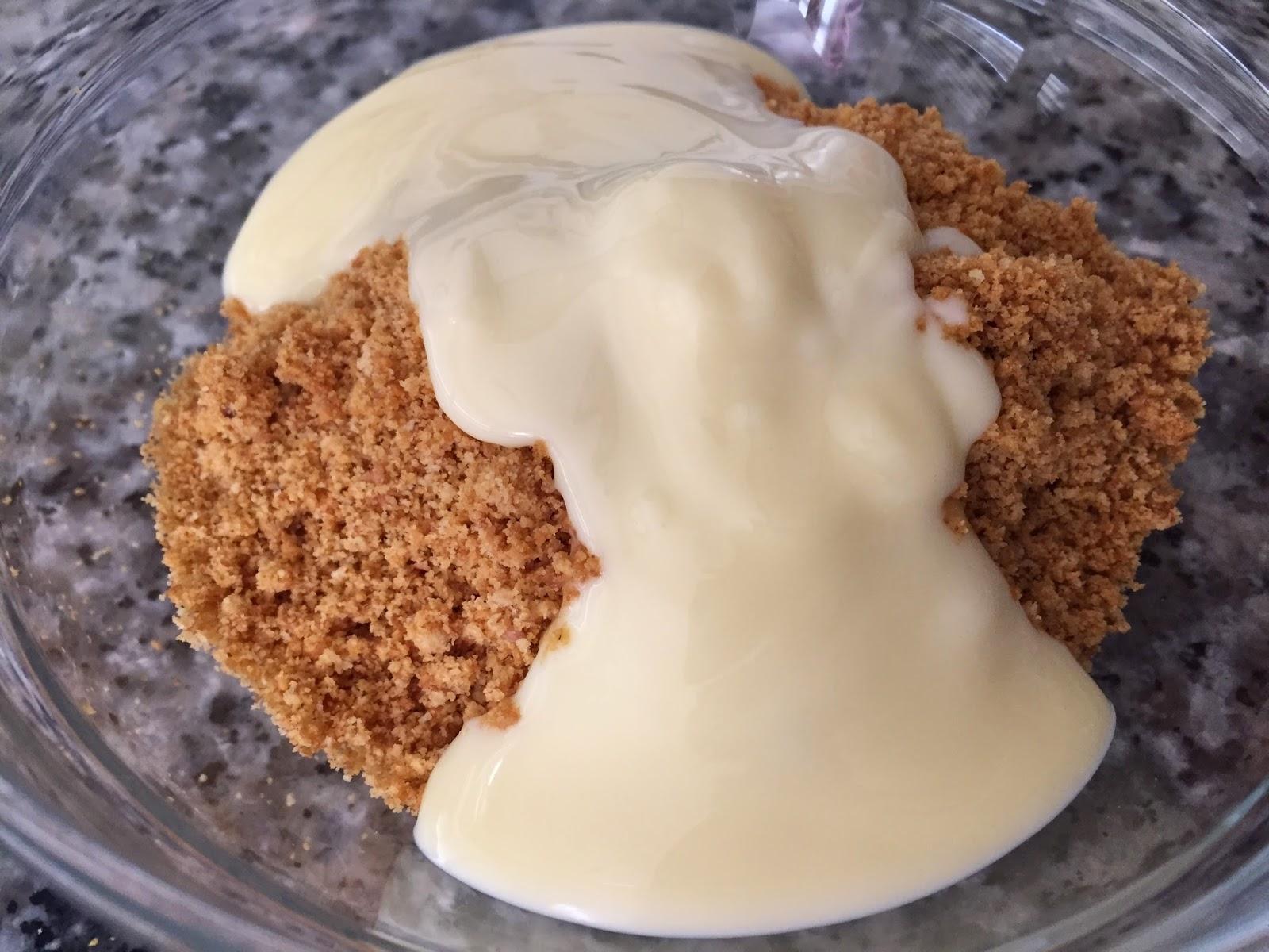 Cheesecake de nocilla blanca y frambuesas, mezclando galletas y mantequilla.