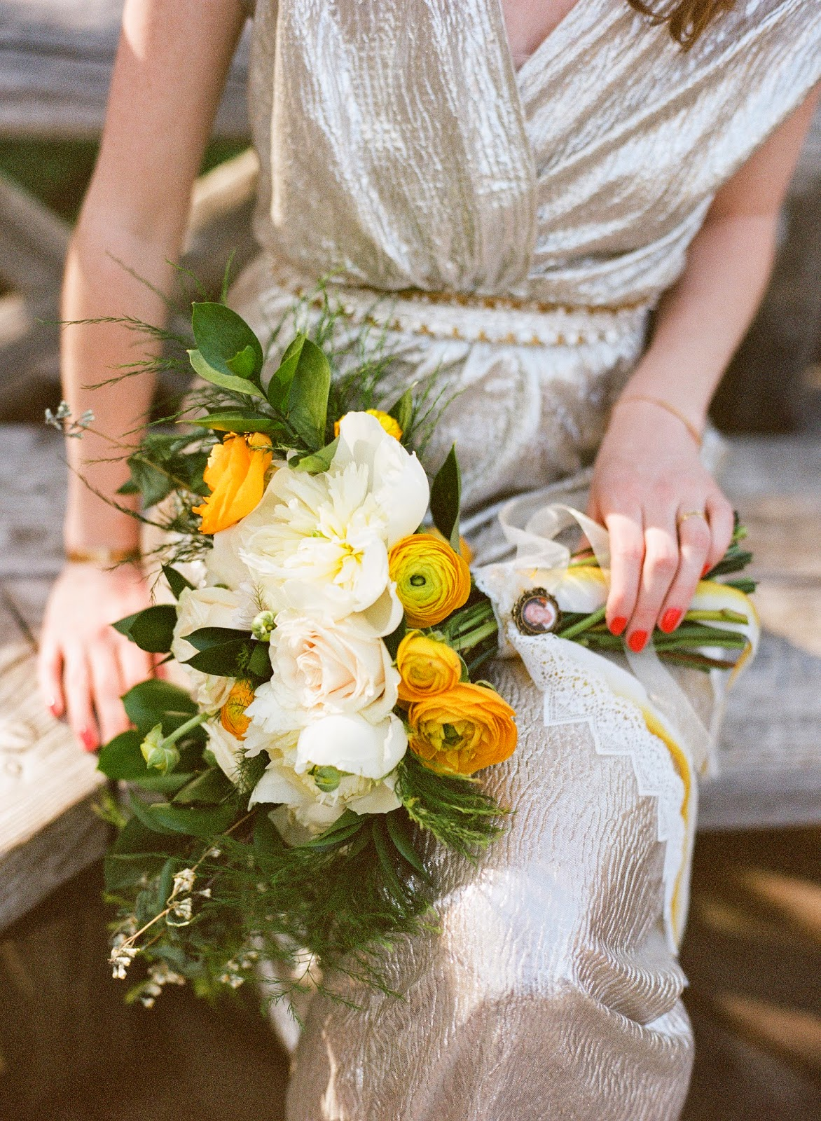 bride in a gold dress holding a yellow ranunculus and white peony spring bouquet with her gold dress in prospect park, brooklyn, new york
