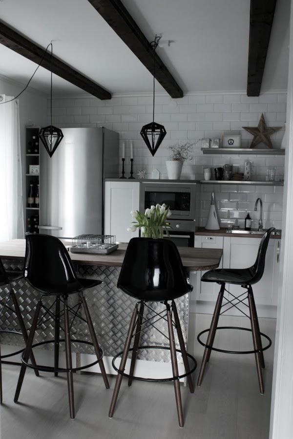 kök i vitt och svart, rostfria vitvaror i köket, miele kylskåp, extra brett kylskåp, hth kök, varberg, vinflaskor vid sidan av kylskåpet, hyllor för flaskor, svarta barpallar, köksö klädd med plåt, inredning, inspiration kök 2014