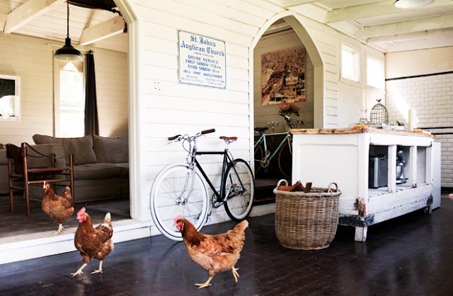 casa tonos blanco y madera con gallinas