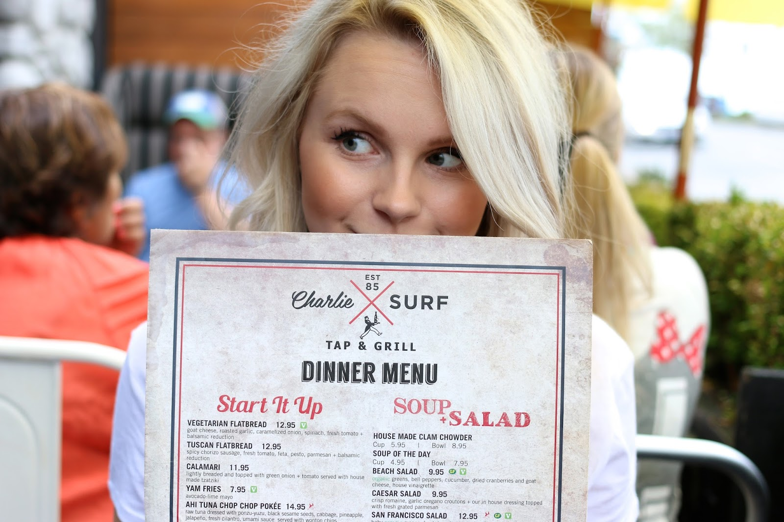 a blonde girl holds a menu