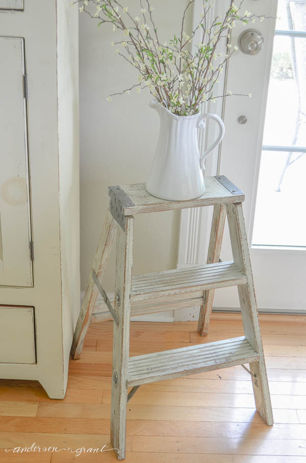 Antique ladder and white pitcher of flowering branches