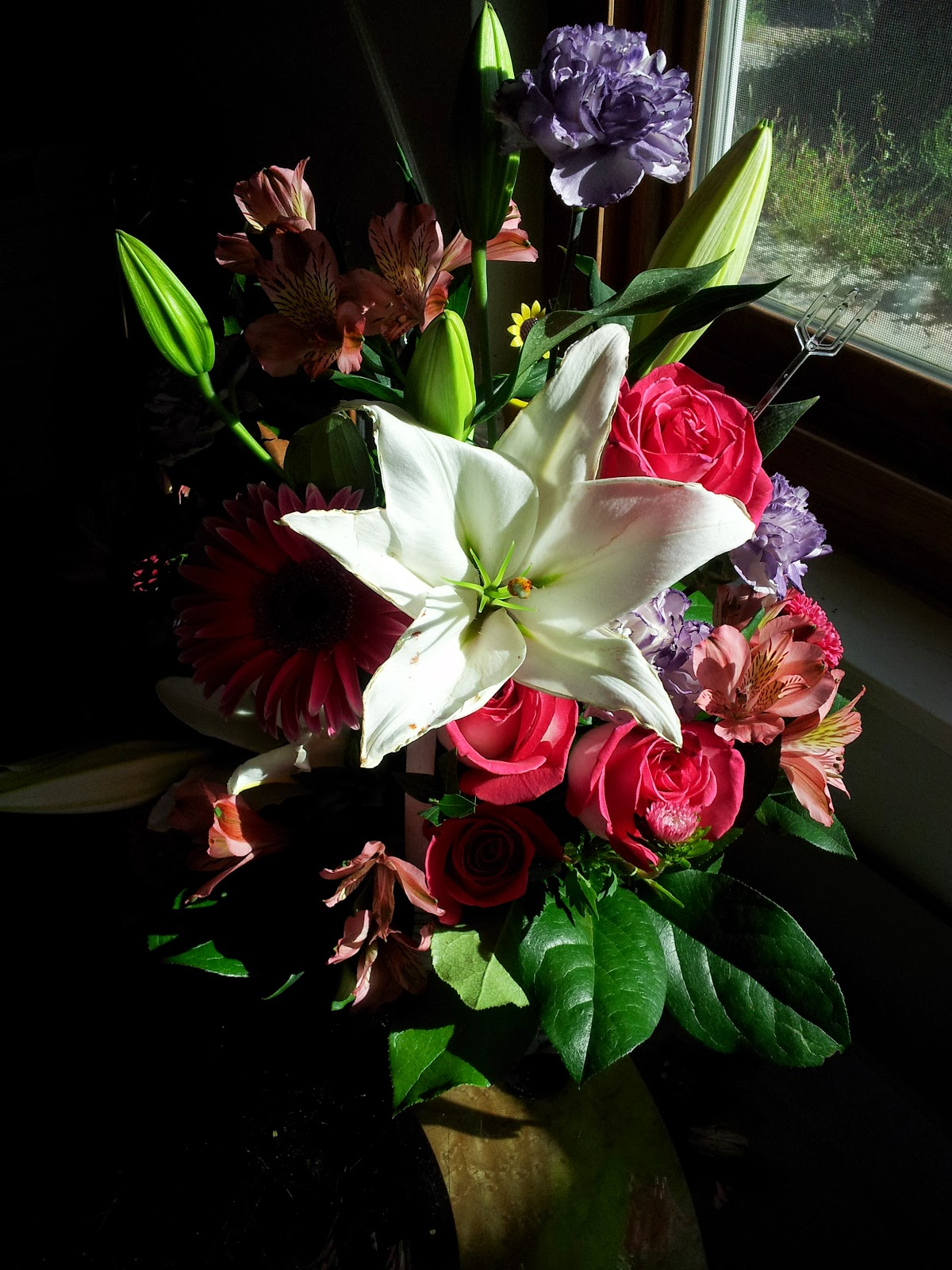 A bouquet of mixed flowers on a sunny windowsill