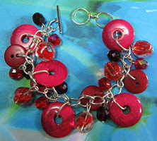 Bracelet has clusters of bright red buttons and beads hanging in pretty charm style design