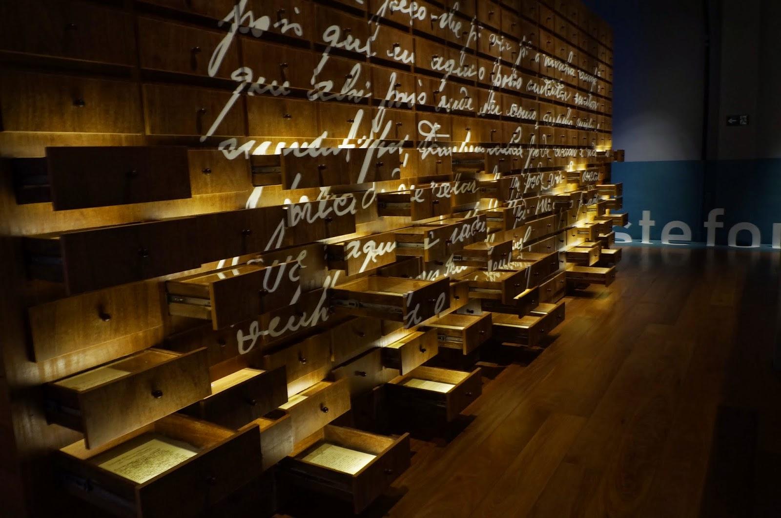 Museu da Imigração - SP: Um paredão de gavetas nas quais é possível observar documentos e ler cartas antigas dos imigrantes