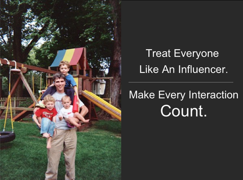 "This is a picture of Randy Pausch hold this children. There is a quote from his on the right side that states""Treat everyone like and influencer. Make every interaction count."""