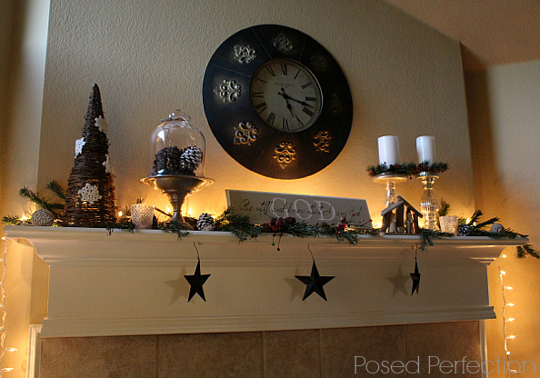 A Tranquil Christmas Mantel with pine bows and pine cones all lit up.