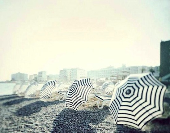 Black And White Striped Umbrellas On Beach In Sun
