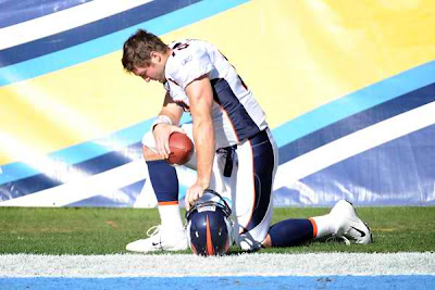 Tim Tebow praying before the game