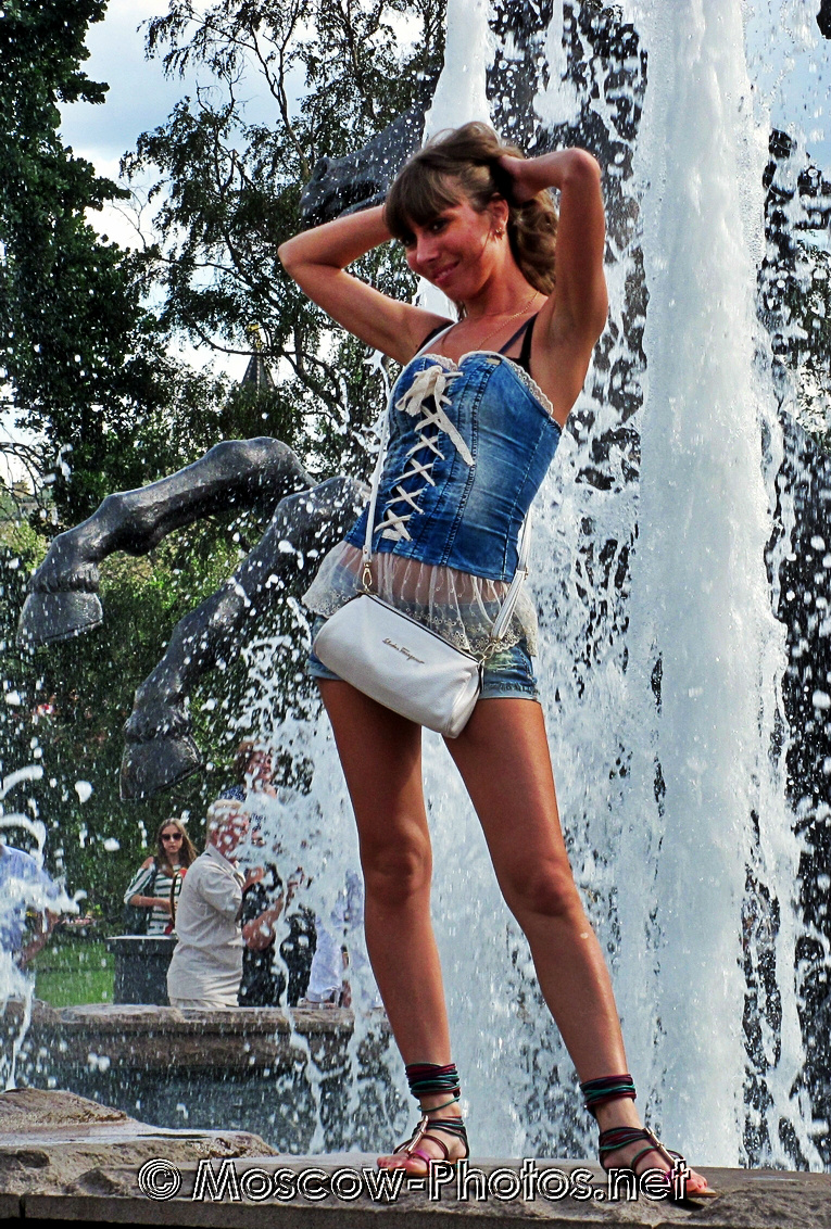Girl posing near a fountain