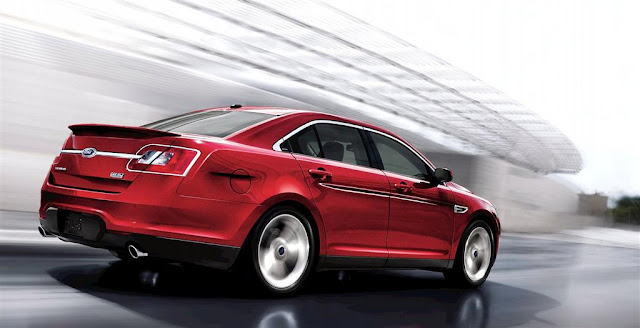 Rear 3/4 view of red 2011 Ford Taurus SHO driving around a building