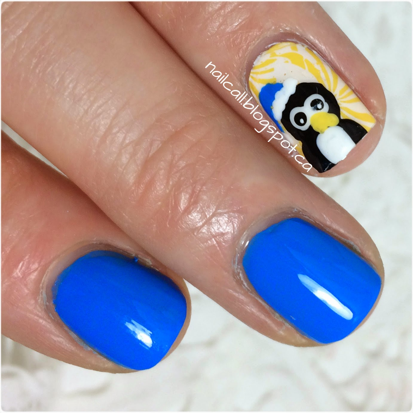 alternate view of blue nail polish with penguin accent nail