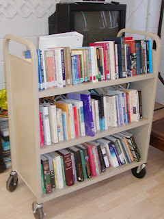 Books shelved on three-level wheeled cart