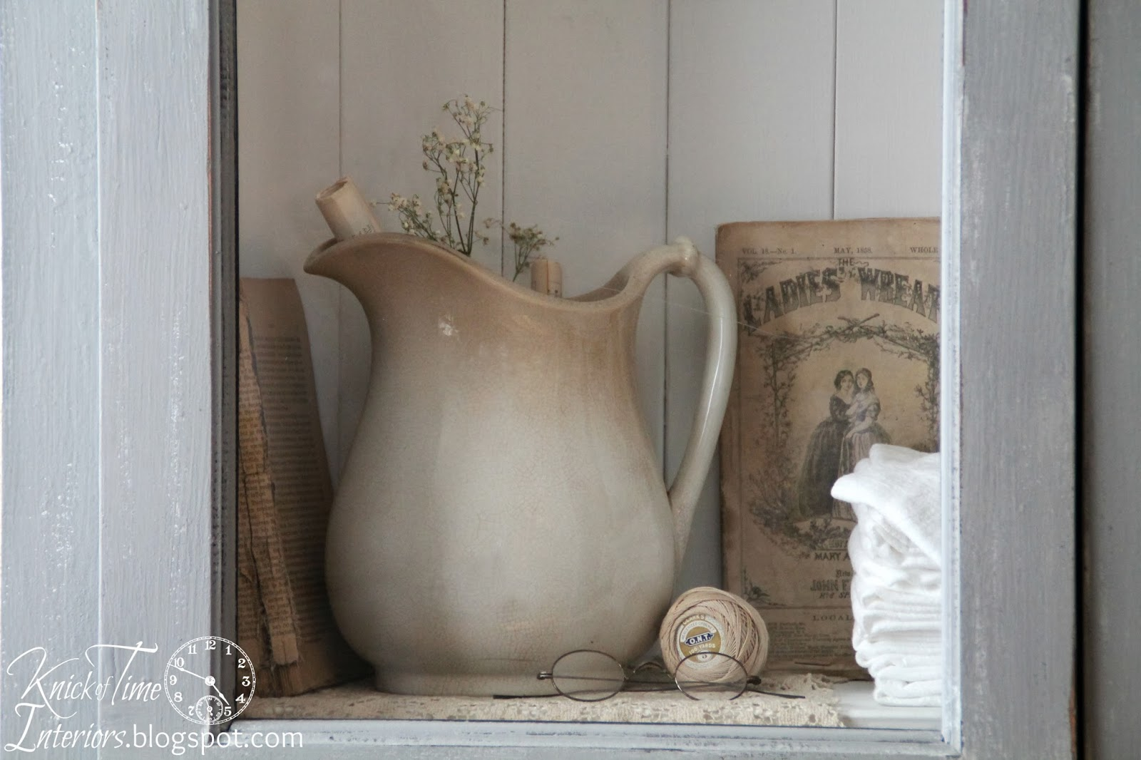 Ironstone, antique books, antique spectacles and flour sack towels inside cupboard via Knick of Time
