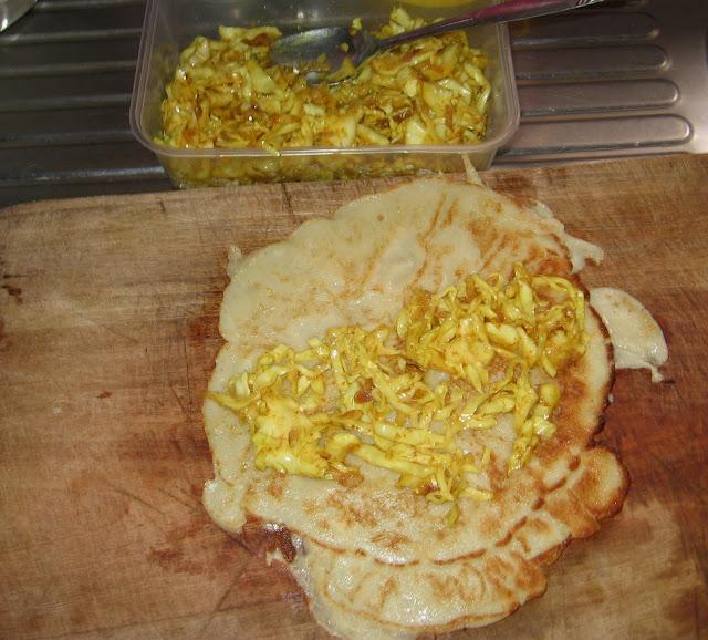 spreading stir fried vegetables on pancake