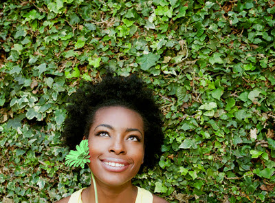 Optimistic black woman holding a flower in front of a wall of ivy