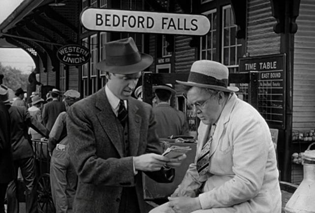 Otro fotograma del film con James Stewart y Thomas Mitchell frente a un cartel de Bedford Falls.