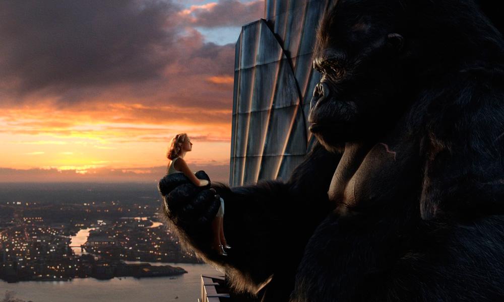 Cena do filme King Kong (2005) onde king kong segura uma mulher na mão no topo de um edificio com a cidade ao fundo