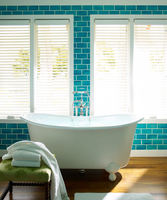 Bathroom with a white clawfoot tub, wood floor, an a wall of blue floor to ceiling subway tiles, windows with white blinds, and wood stool with green cushion is being used as a towel holde