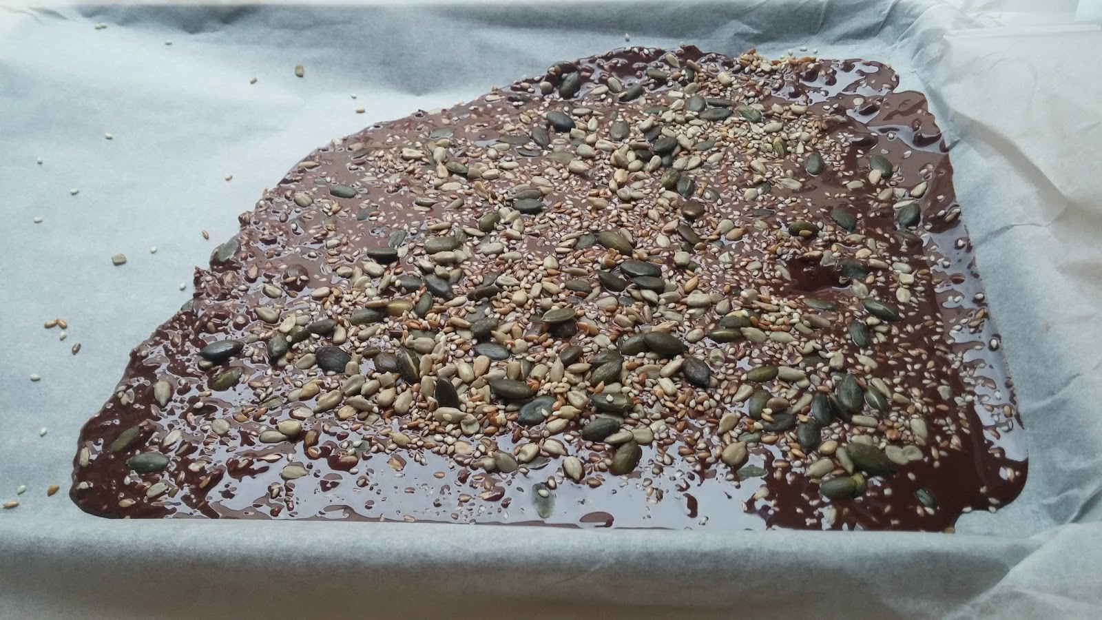 Melted dark chocolate poured out onto parchment paper topped with seeds and sea salt waiting to set