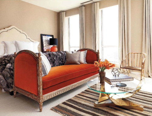 seating area at foot of bed, couch and coffee table at foot of bed, bedroom, coffee table, couch at foot of bed, interiors, interior design, interiors inspiration, orange settee, white headboard, moroccan headboard, brass coffee table, striped rug, fur on bed