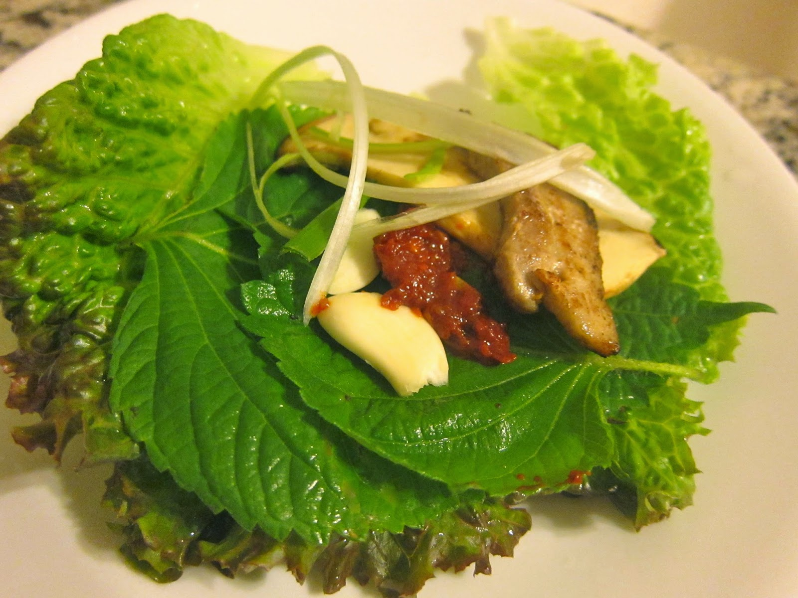 Grilled pork belly with Korean kochu jang, dang jang, perilla leaves and red leaf lettuce