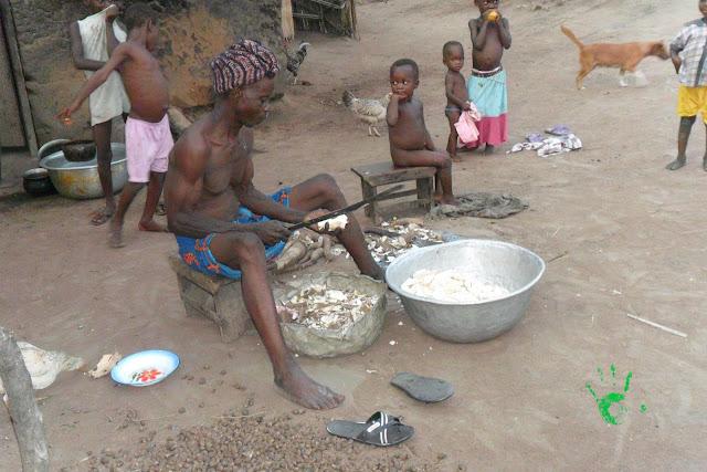 Padre del villaggio africano con manioca