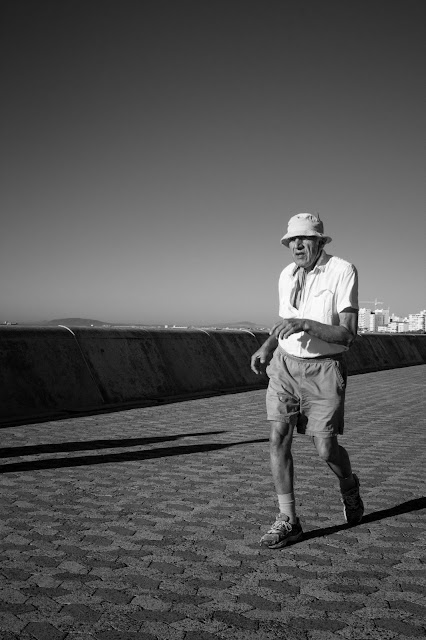 Street photograph of elderly man running on promenade in Cape Town