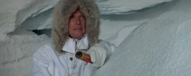 Roger Moore as James Bond in A View To A Kill (1985), readying to use a smoke distress flare orange smoke bomb to blow up an orange helicopter after a downhill snowboard chase, he wears a white parka trimmed with fur