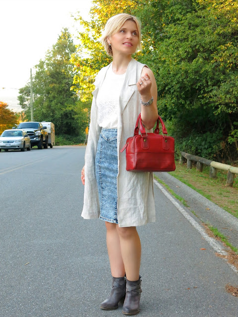 styling an acid-wash denim pencil skirt with a lacy top, sleeveless linen coat, and booties