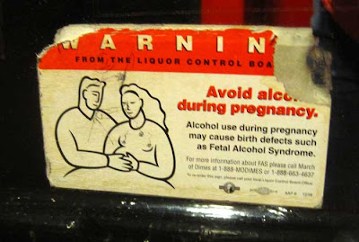 Printed warning on a mirror, saying alcohol consumption during pregancy causes fetal alchohol syndrome
