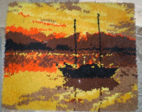 A painfully ugly hooked rug depicting a small brown boat against a violently orange, brown, and yellow sunset.