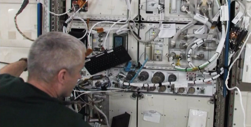 Steve Swanson works on a rack inside the Kibo laboratory. Image Credit: NASA TV