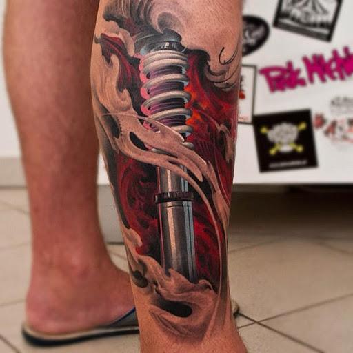 tatuaje en la pantorrilla con un brazo de suspension