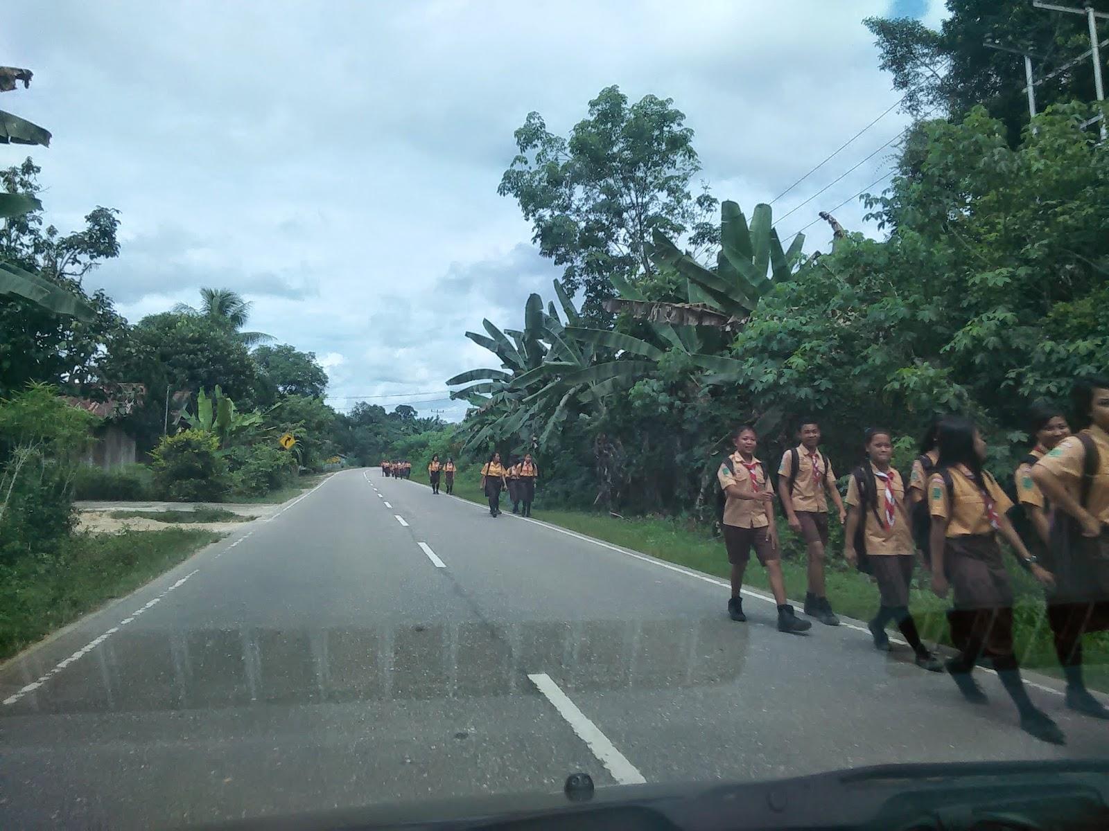 Anak-anak murid  berjalan kaki pulang dari sekolah