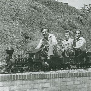 Foto de Walt Disney brincando com a locomotiva montada em sua casa